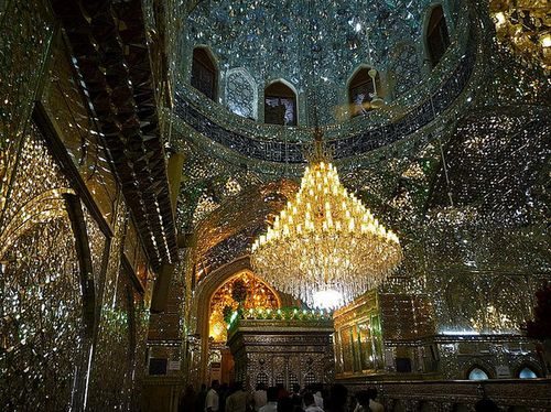 A brilliant, glittering mausoleum in Iran named Aramgah-e Shah-e Cheragh. The walls are made of tiny mirrors illuminated by the soft glow of a center chandelier.