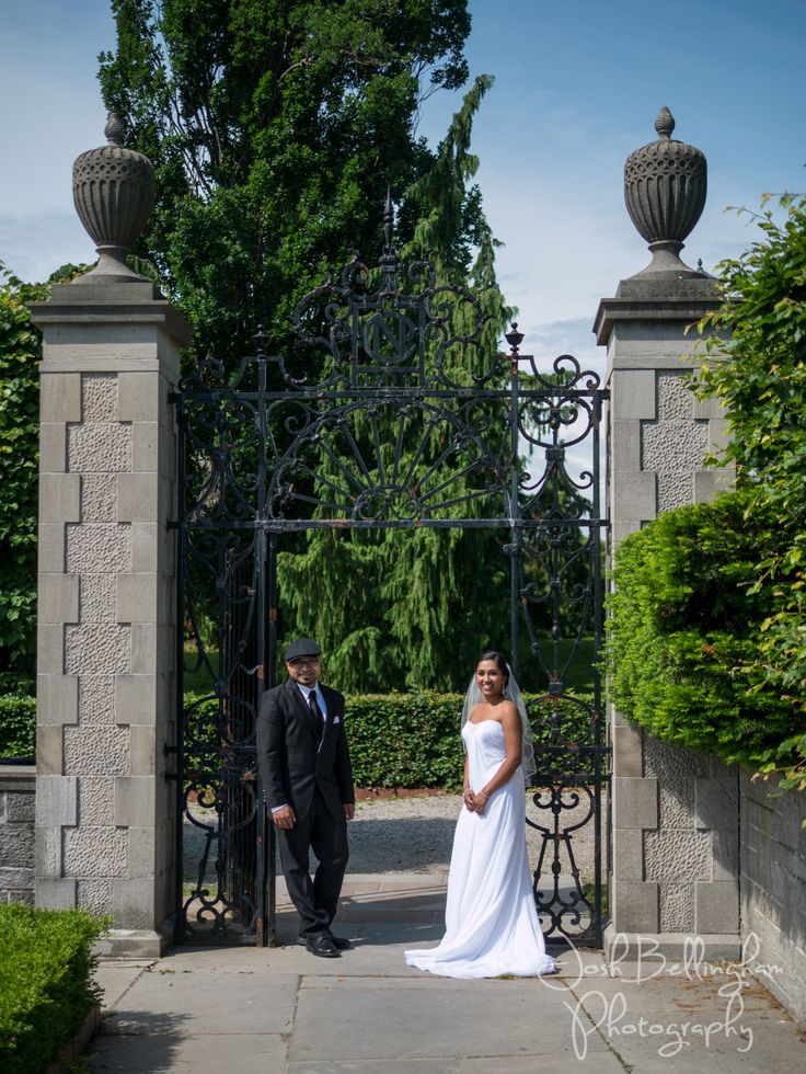 Bride and groom photograph at Oakes Garden Theatre. Cute bridal photo at large gates in Niagara Falls Canada. #JoshBellinghamPhotography