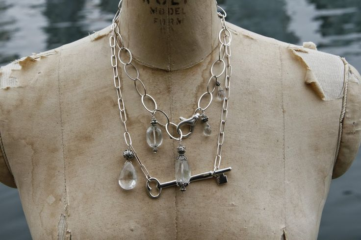 Two sterling silver necklaces. One with an antique key and a large rutilated quartz pendant. The other with four phantom quartz pendants and a decorative silver lobster clasp.
