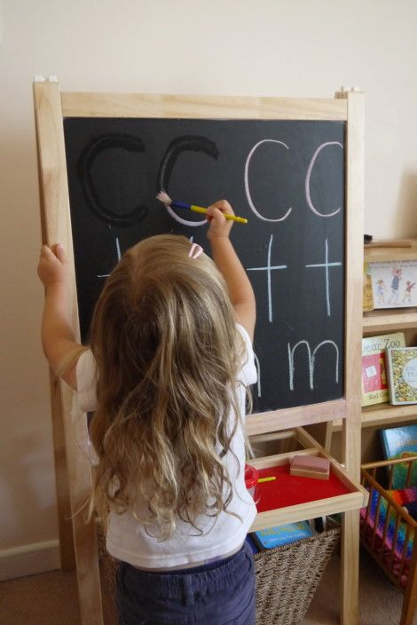 Learning letters-painting over chalked letters using water.