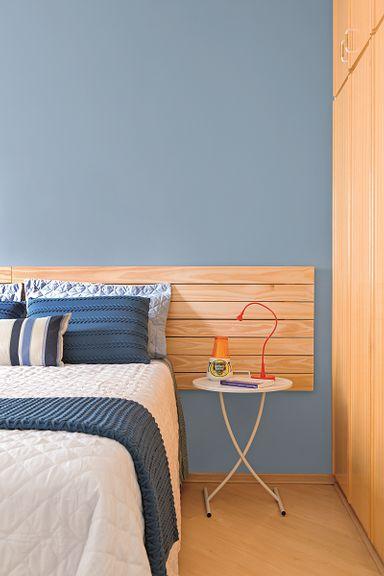 """Madeira é sempre uma boa pedida quando se quer agregar uma sensação de acolhimento. """"Como o apê já tinha o material em tom claro no piso e no armário, escolhi uma cabeceira de pínus ripada com acabamento cru"""", conta o arquiteto Neto Porpino. A tonalidade faz uma bela composição com o azul da parede – o profissional manteve a proposta da paleta de azuis do apartamento, mas no dormitório escolheu um rebaixado e puxado para o cinza, a fim de deixar a atmosfera relaxante. Cor Mergulho Seren..."""