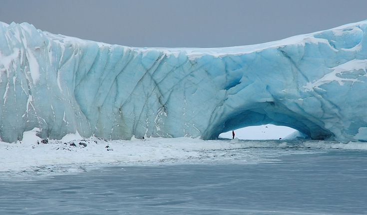 A person stands underneath a natural arch in a glacier at Norsel Point, Anvers Island, Antarctica on July 30, 2006.