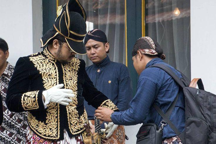 """Sebuah pengabdian Seorang abdi dalem kraton tengah membetulkan lengan baju seorang bangsawan menjelang upacara grebeg maulud di kraton Yogyakarta.  Upload…"""
