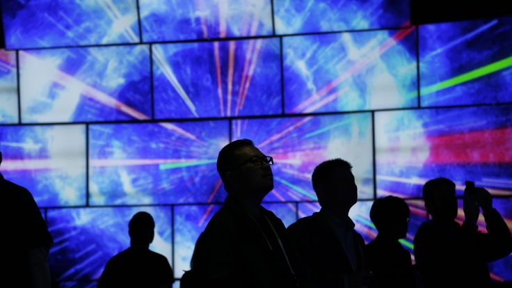 Attendees look at a display of Samsung SUHD Quantum dot display TVs at the Samsung booth during CES International, Friday, Jan. 8, 2016, in Las Vegas. (AP Photo/Gregory Bull)