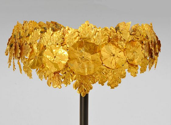 Hellenistic Gold Oak Wreath, c. 4th-3rd Century BC A Greek Hellenistic diadem wreath comprising numerous projecting sprays of sheet-gold oak leaves in two sizes with serrated edges & veins, a large central rosette with two smaller similar roundels flanking. The most famous of such wreaths is the example from Vergina in the tomb of Philip II of Macedon, father of Alexander the Great.