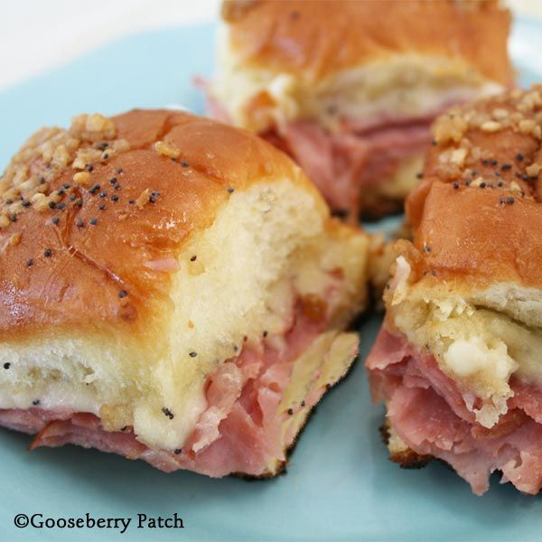 """Cut rolls in half; set tops aside. Place bottoms in a lightly greased 13""""x9"""" baking pan; they should just fit. Layer ham and cheese on top. Sprinkle with poppy seed; replace roll tops. In a bowl, combine remaining ingredients. ½ c. butter, melted 1-1/2 T. Dijon mustard 2 T. dried, minced onion 1-1/2 t. Worcestershire sauce Pour over top. Bake, covered with aluminum foil, at 350 degrees for 15 to 20 minutes. Cut into squares to serve."""
