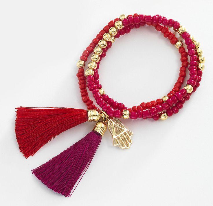 Trío de pulseras de 4 baños de oro de 18 kt y chaquiras en color rojo y fucsia y un amuleto de la buena suerte. Modelo 415756L.