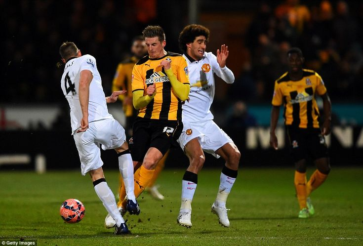 Cambridge United's Liam Hughes takes on both Phil Jones and Marouane Fellaini in an attempt to win possession for his team