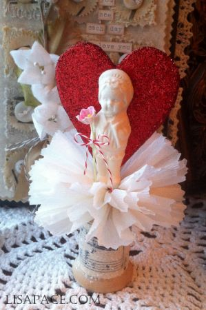 Lisa Pace ~Valentine Home Decor Accent using handmade penny candy dolls, vintage sheet music and wooden spool.