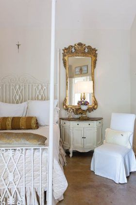 """Again, the neutral white palette allows special pieces to take center stage like the custom headboard Julie created from a discarded garden gate she found on the side of the road. """"I'm somewhat of a 'dumpster diva,'"""" Julie admits, and allows what was once trash to become a highlighted treasure in her room."""