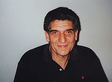 "Andrew ""Andreas"" Katsulas (May 18, 1946 – Feb. 13, 2006) was a Greek-American actor known as Ambassador G'Kar in the science fiction television series Babylon 5, as the one-armed villain Sykes in the film The Fugitive (1993), and as the Romulan Commander Tomalak on Star Trek: The Next Generation.  He also played Vissian Captain Drennik in the Star Trek: Enterprise episode ""Cogenitor.""  He was born in St. Louis, Missouri to a working-class Greek-American family."