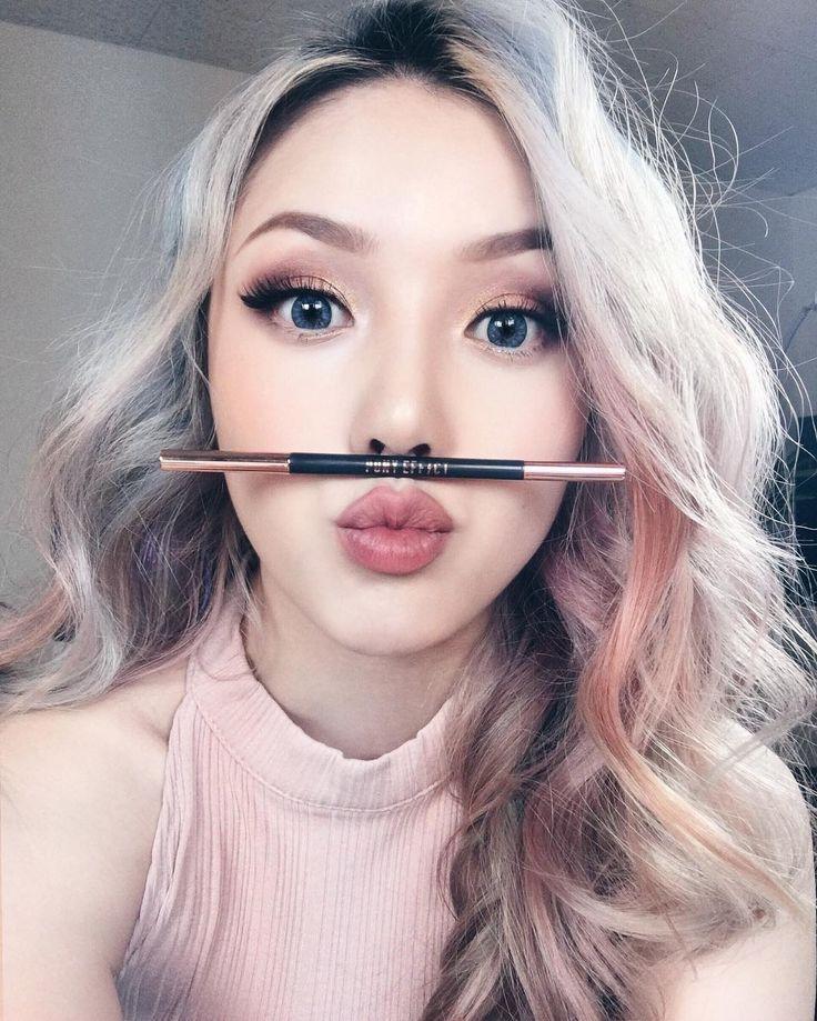 Flawless skin, natural brows, smoky eyeshadow, winged eyeliner, full lashes, blue circle lenses, coral blush, pink tinted lips.