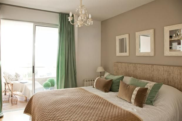 Sobre el respaldar tapizado en rafia, tres espejos heredados. Pie de cama en pana matelasé con borde en crochet y almohadones color visón y aquamarina (todo de Prágmata)..