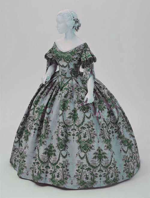 Late 1850's early 1860's. Ball gown by the neckline. Sleeves cover the elbow, elegantly. For a woman of a certain age?
