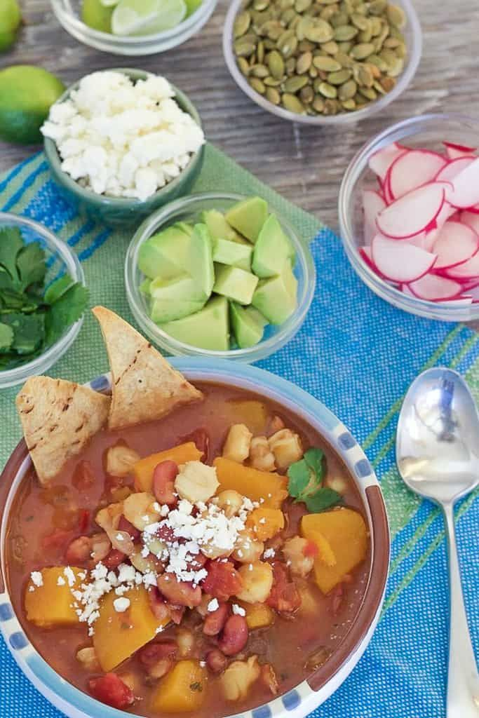 Easy one-pot Slow Cooker Butternut Squash Posole made with dried chiles, hominy and pinto beans. Garnish with cotija cheese, avocado and cilantro. via @lettyskitchen