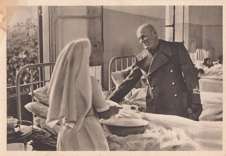 The Duce of the Kingdom of Italy shakes the hand of a Roman Catholic nurse while on visit to a military hospital.
