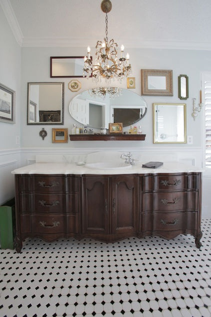 Bathroom with chandelier, eclectic mirror collection over vanity, repurposed dresser as vanity, black and white tile floors. bathroom by Lindsay von Hagel