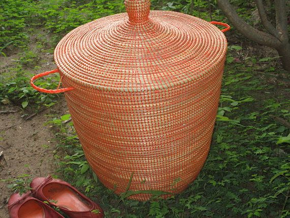 This handwoven senegalese style Basket is on Sale.!! It features a flat lid and is tangerine coloured. The shape is wider and lower, instead of