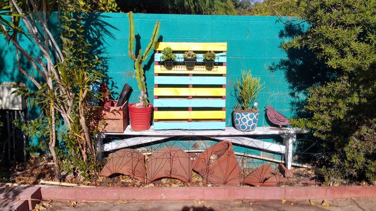 my new southwestern landscaping with new painted bench and new painted pallet with cactus and other succulents. broken clay pots to make it look old style