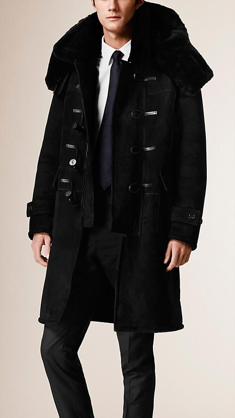 Burberry shearling duffle coat with a smooth outer and soft, textured reverse. An oversize hood wrap with smooth leather buckle straps and double zip and toggle closure keep the elements at bay. Discover the men's outwear collection at Burberry.com