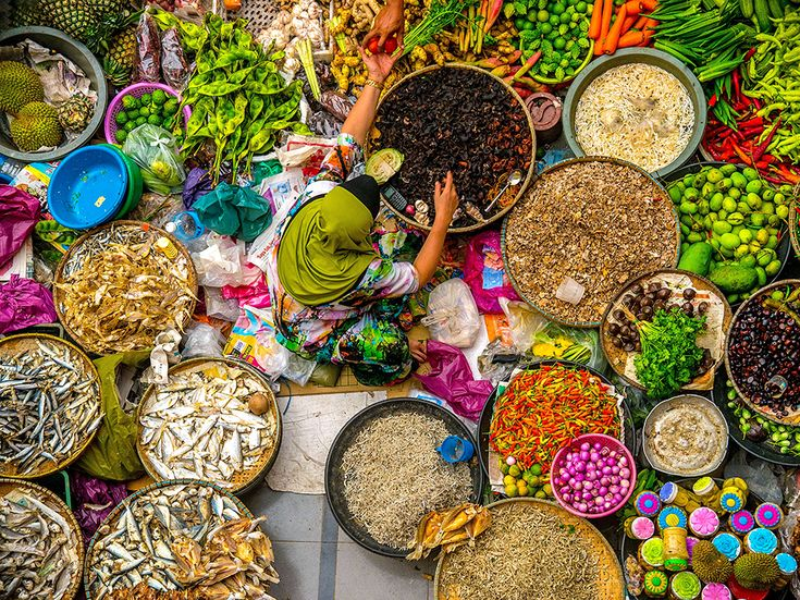 Fresh produce and baskets of fish surround a woman at the Siti Khadijah market in Kota Bharu, Malaysia. The city is close to the Thai border. [Photo by Duratul Ain D., National Geographic Your Shot]
