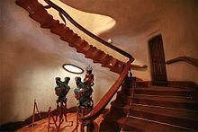 La Casa Batlló antoni Gaudi Barcelone Espagne : en bois de chêne et incorpore dans son limon des éléments sculptés qui évoquent les vertèbres d'un animal préhistorique. L'ensemble de ces éléments forme une spirale sinueuse qui couvre un angle de presque 180 °, prenant la forme de l'échine d'un monstre géant dans sa grotte. La rampe qui longe l'escalier est munie à ses extrémités d'éléments décoratifs : une tige de métal avec une sphère rouge entourée de deux rubans de fer soutenant une…