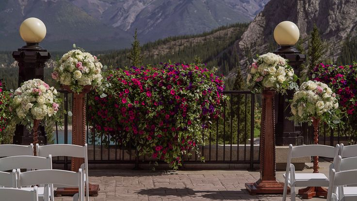 Pink and white florals with greenery on wooden pedestals for a beautiful outdoor summer wedding ceremony on the Fairmont Banff Springs Terrace!  www.flowersbyjanie.com