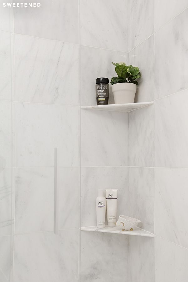 Luxe uptown bath with luxe marble square wall tiles and custom marble shower shelves from Home Depot.