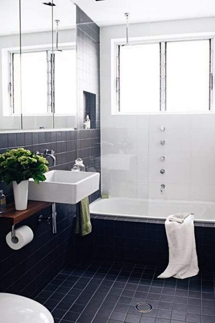 After | The sleek renovation - dramatic chocolate square tiles contrast with the clean white tiles for a thoroughly...