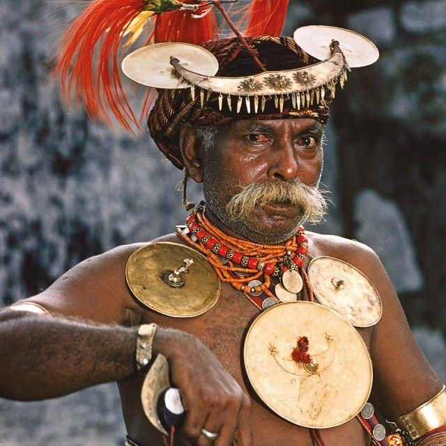 Dom Antonio-pemimpin suku di Vila de Ainaro, Timor Portugis-mempersiapkan tarian perburuan kepala, yang menggunakan melon sebagai pengganti tengkorak. Ekor kuda menjuntai dari tanduk kerbau di kepala Dom. Helen dan Frank Schreider bercerita bahwa di Timor, perburuan kepala baru-baru ini dilarang lagi. Pasangan itu memulai penjelajahan dunia pada 1954. Di dekat Vila Nova di Malaca, pada rumah2 tinggi berhias, terdapat pajangan yang mengingatkan kita pada adat kebiasaan ini, berupa cangkang