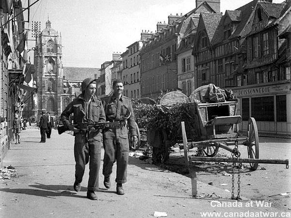 27 août 1944 : des soldats canadiens progressent à côté de deux charrettes allemandes dans les rues de Elbeuf.