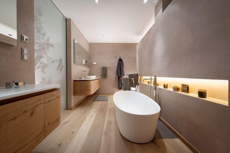 Modernes Badezimmer mit freistehender Badewanne in einem Design Apartment in den Kitzbüehler Alpen. Die weiße Wanne passt perfekt in das holzfarbene Bad.