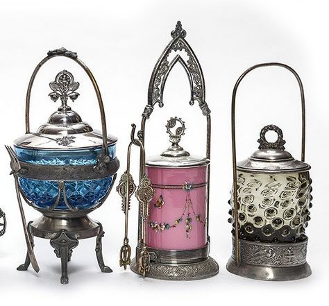 group of three Victorian pickle castors in silverplate frames, one with a barrel shaped insert green tint & random hobnail, the second is a Prussian blue insert with pressed floral pattern and the third is a pink satin with garlands and butterflies.