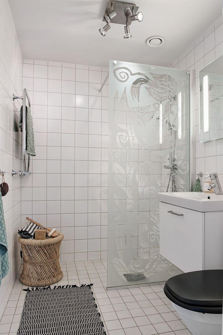 Lemn deschis la culoare, accesorii maro, tapet cu flori și o ușă simpatică în alb și negru, toate în decorul acestui apartament din Suedia.