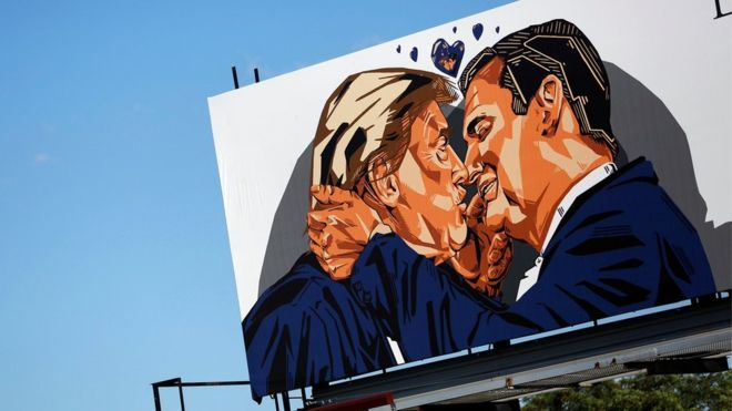A billboard erected in advance of the Republican National Convention depicts U.S. Republican presidential candidate Donald Trump kissing former presidential candidate Sen. Ted Cruz - July 2016