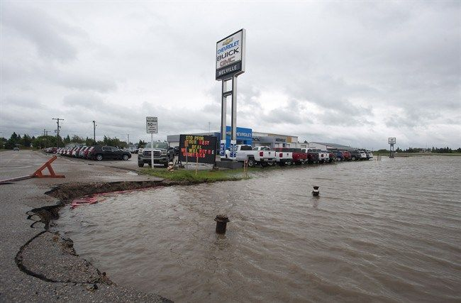 The ditches overflow with rain water near a car dealership in Melville, Saskatchewan on Sunday, June 29, 2014 . Highways are closing and com...