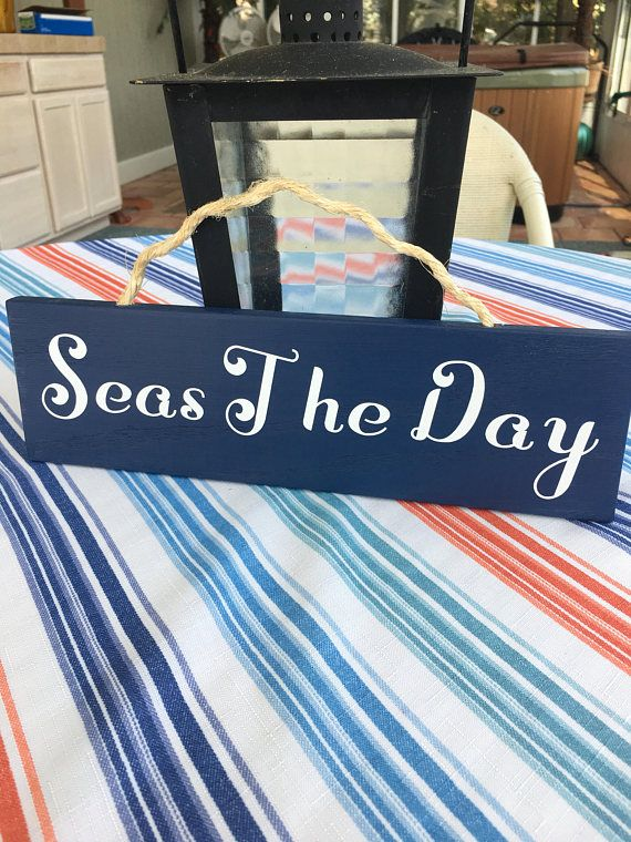 Seas The Day Wood Sign   This high quality wood sign is crafted from solid oak hardwood. The edges have been sanded and given slightly rounded edges to soften the appearance. The signs are painted with HGTV Home collection colors from Lowe's. The lettering and was die cut from ling lasting white vinyl.    #seastheday #nautical #nauticalsigns #coastal #seas #summervacation #oceanlife #inspiration #handmade #woodsign #madeintheusa
