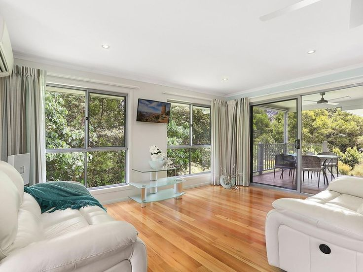 Open Living area with beautiful timber flooring + surrounded by greenery | Tru-Built Builders Queensland