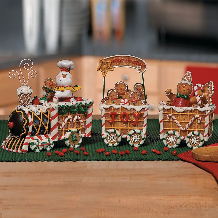 "The Gingerbread Express Train. Loaded with decorative treats for the eye and gingerbread travelers, this sweet all-resin Christmas train is a perfect holiday touch for your kitchen or a dessert table and a darling Christmas gift for a collector. 5""H x 12 1/2""L overall."
