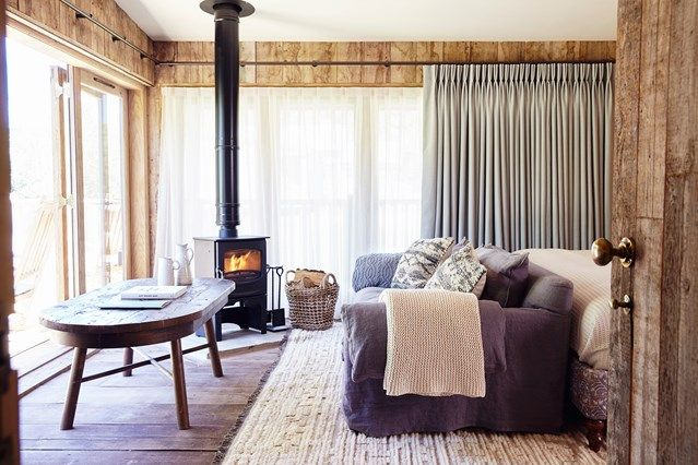 Sitting room at Farmhouse by Soho House featuring a wood burner making the area cosy and warm in the winter months. HOUSE - design, food and travel by House & Garden.