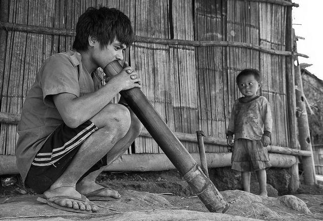 Man smoking wooden bong while his son observes, Lahu village near Luang Namtha, Laos, December 2012 (by Freek Nijenhuis)