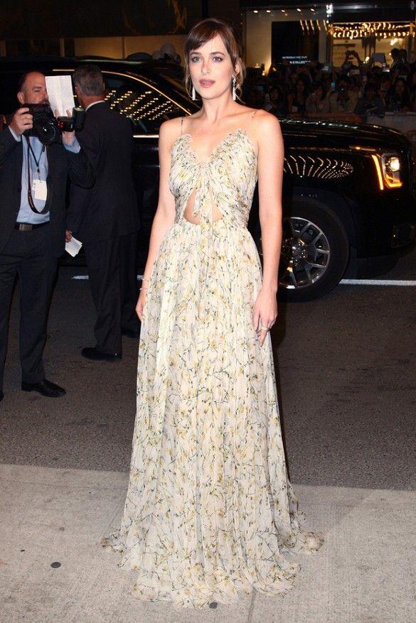 Dakota Johnson wears a floral cutout Alexander McQueen gown with statement earrings
