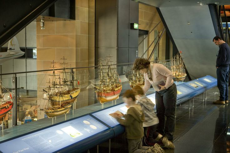 Museum of Sydney. Visitors looking at the first fleet ships. This is a long display of models of the first fleet ships behind a graphic.