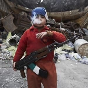 Kids should not have to live like this.  Ahmed, the son of a fighter in the Free Syrian Army, smokes and stands guard with an AK-47 in front of a barricade protecting rebels from snipers.  He is seven years old.
