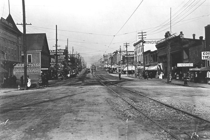 "1909 Columbia looking east from  Central Hotel (near 8th Street). This photo was taken before pavement & lighting.  The street was paved and improved, lighting was put in by 1911. The photowas in an album titled, ""Views Showing Hassam Pavement as Laid by the Hassam Paving Co. of B.C. Ltd."" On the south side of Columbia is: Edison Theatre at 772, K. Kirikopoulos boots &shoes at 768, Royal City Transfer Co. (H.A. Belya & Co.) at 766, the Tram Barber Shop at 764, BCER at 756."