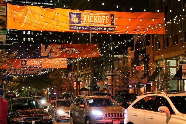 """Larimer street (see more on @streetvogs) in downtown Denver, known for its trendy shops, classy restaurants, artsy events and lighted canopy, is decorated above with Broncos vs. Panthers banners to celebrate the first game of the season."" @sarabeetsphotography for @streetvogs"