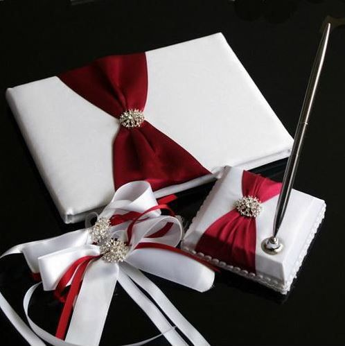A Must Have Wedding Accessory Piece That Adds A Sweet & Classy Touch To Your Special Day That Will Be Filled With Romantic Memories For Anniversaries To Come!   The pen holder comes with a slim stylish silver pen. The deep red ribbon enhances the gorgeous white satin on the wedding guestbook. T...