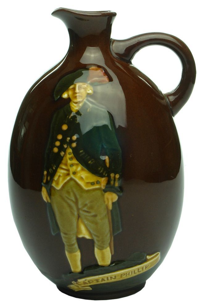 Embossing: (Captain Phillip) / Captain Phillip // (Back of Sailing Ship - First Fleet) / 1788-1938. Base: Dewar's / Whisky / Lion over a Crown / Made in England / Royal Doulton / England. Type: Spirits Whisky/Whiskey /  Era: 1938 /  Variety: Multi-coloured ceramic Kingsware decanter. About 20 oz. /  Height: 187 mm /  Condition: Very Good.  The handle has been broken at some stage and reglued, then the joins painted.  A bit of dust and grime.  Some scratches. /  Grade: 7 /  Estimate:  $ 75…