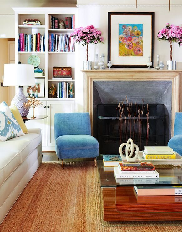 Cynthia Collins - Chic living room with Paris flea market blue slipper chairs in front of fireplace. Living room built-in cabinets filled with antiques and flea market finds. Living room features white linen 3-cushion sofa filled with white and blue ikat pillows next to antique end table with white fish scales lamp and art deco coffee table over jute rug.