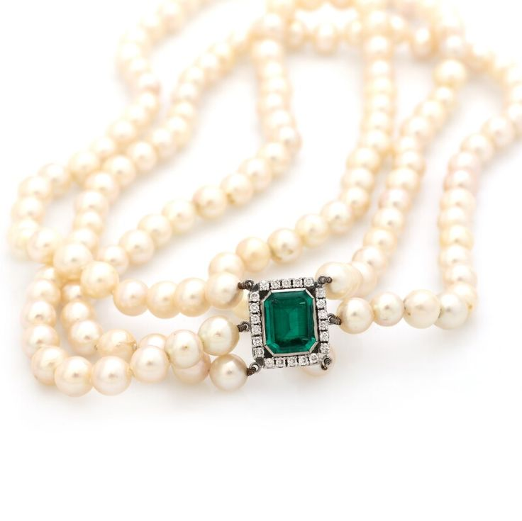 A Three strand pearl necklace with cultured pearls and a tourmaline and diamond clasp set with an emerald-cut tourmaline encircled by numerous brilliant-cut diamonds weighing a total of app. 0.55 ct., mounted in 14k white gold. Colour: G. Clarity: SI. Pearl diam. app. 7.3-8.3 mm. L. app. 43-46 cm. Circa 1970.